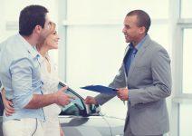 Un jeune couple discute avec un vendeur conseiller de voiture