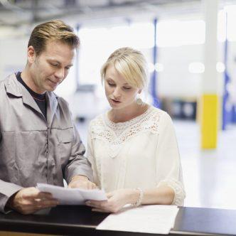 Un mécanicien montre un papier à sa cliente sans son garage automobile