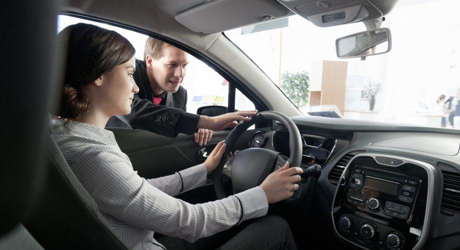 Jeune femme essaye une voiture , un conseiller lui parle par la fenêtre